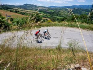Two road cyclists on tour in the Apennin on a lonely mountain road near Savignano di Rigo province of Rimini in the Emilia-Romagna region