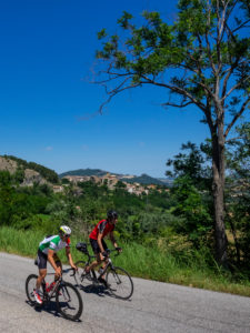 Two road cyclists on tour in the Apennin on a lonely mountain road near Talamello, province of Rimini in the Emilia-Romagna region.