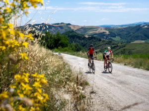 Two road cyclists on tour in the Apennin on a lonely mountain road, gravel road, Strade Bianchi near Predappio, Province of Rimini in the Emilia-Romagna region.