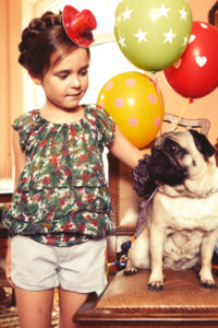Girl with Party hut and stylish pug with balloons