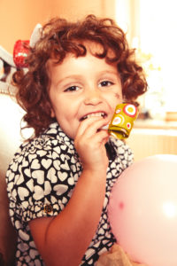 Curly brown haired Party Girl has fun with party horn and pink balloon