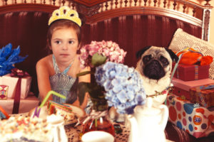 Party Girl and pug sitting on a sofa and waiting