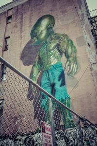 Backyard scene Graffiti of a green superpower baby, Little Italy, Manhattan, New York, USA