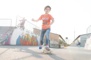 Boy in the orange T-shirt riding skateboard