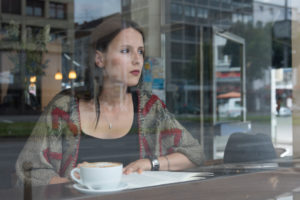 Young woman behind window while reading in the café, thoughtful, semi-portrait