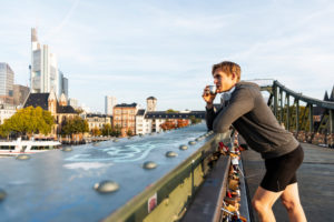 Sporty man has a break jogging in the town, Frankfurt on the Main, Hessen, Germany