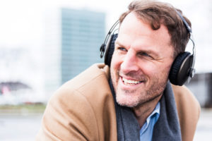 Businessman hears outside music with earphones, portrait