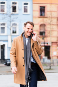 Businessman on the way to work with Smartphone, half portrait