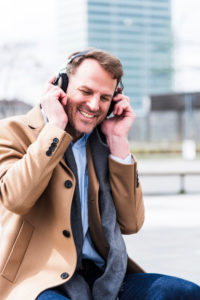 Businessman hears outside music with earphones, half portrait