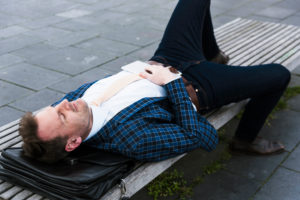 Businessman has a break on a park-bench
