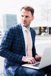 Businessman outside with laptop, half portrait