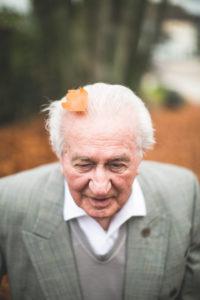 Senior beim Herbstspaziergang, Blatt auf dem Kopf