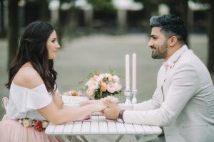 junges Paar am Tisch, verliebt, glücklich, Hände halten, Blickkontakt,