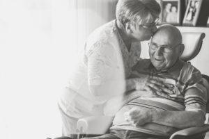 Seniorenpaar, Mann im rollstuhl, Frau küsst ihn auf die Stirn, s/w