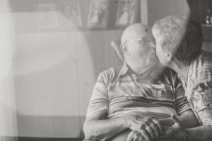 Glückliches Seniorenpaar Zuhause, küsst sich, s/w