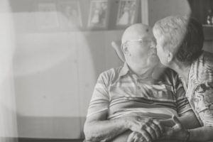 Happy older couple at home, kisses each other, s/w