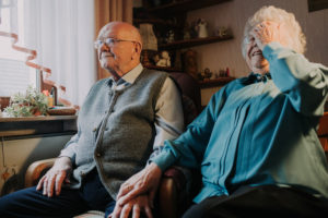 older couple, home, woman smiles