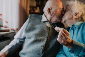 Seniorenpaar , Kuss, Frau hält ehering in die Kamera,