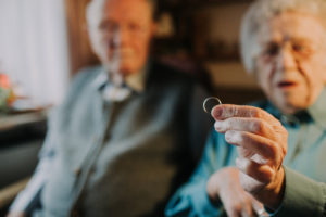 older couple, woman holds wedding ring into camera