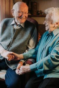 Seniorenpaar hält sich an den Händen, glücklich, lachen,