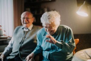 older couple sits laughingly in the living room