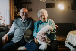 older couple with poodle in own home