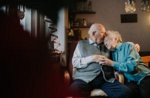 Seniorenpaar kuschelnd im Wohnzimmer