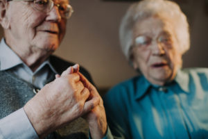 Seniorenpaar hält sich an den Händen,