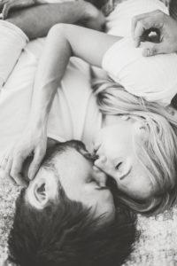 Junges verliebtes Paar zuhause im Bett, Halbportrait, s/w