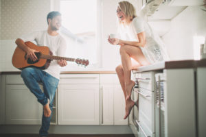 Young couple in love making music at home,