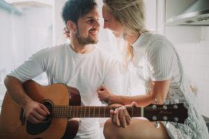 Junges verliebtes Paar zuhause beim Musizieren, Halbportrait