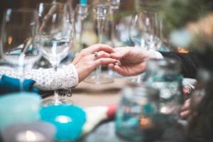 Brautpaar an gedecktem Tisch bei indianischer Hochzeit, Hände, Berührung, Zärtlichkeit, close-up