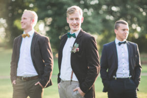 Bridegroom and groomsman outside, half portrait