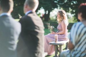 Gäste und Trauzeugin bei alternativen Hochzeit im Freien, Halbprofil