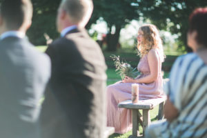Guests and witness at alternative wedding outside, half profile