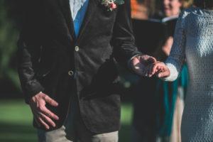 Alternatives Hochzeitspaar bei spiritueller Trauung im Freien, Detail, Hände halten