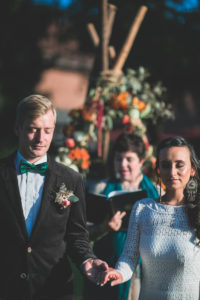 Alternate bridal couple at spiritual wedding ceremony outdoors, half portrait