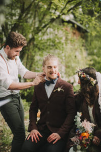 Alternate bridal couple at wedding ceremony outdoors, witness ties bridegroom the bow tie, excitement, nervousness