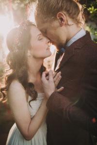 Bride and groom at alternative wedding celebration outside, half profile