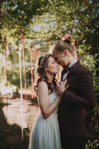 Bridal couple at alternative outdoor wedding, half profile