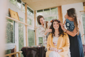 Alternative wedding, preparation, friends decorate bride with floral wreath