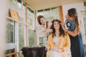 Alternative wedding, preparation, friends decorate bride with floral wreath