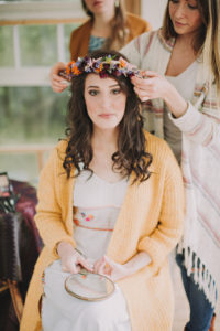 Alternative wedding, preparation, girlfriends decorate bride with floral wreath