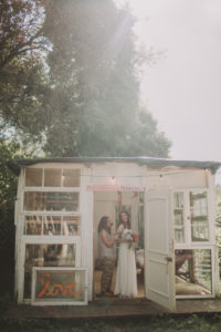 Alternative wedding, preparation, bride and girlfriend in garden pavilion