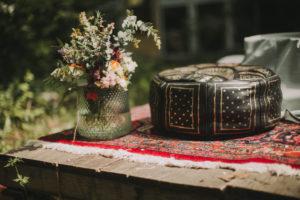 Sitzkissen und Blumenschmuck bei alternativen Hochzeitsfeier, close-up