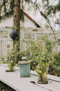 Garden table with glasses and decoration: lantern, flowers and twigs