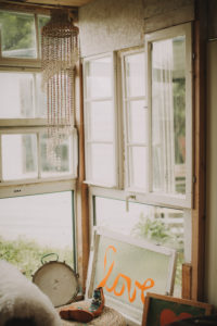 Alternative interior furnishing in a garden shed, window with the inscription 'Love'