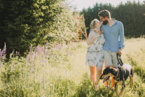 Couple in love walk with dog in a meadow,