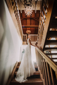 Bride in long white dress is standing on a stair,