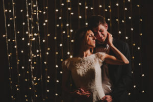 Bridal couple in love, standing, hug, half portrait, curtain of lights, detail,